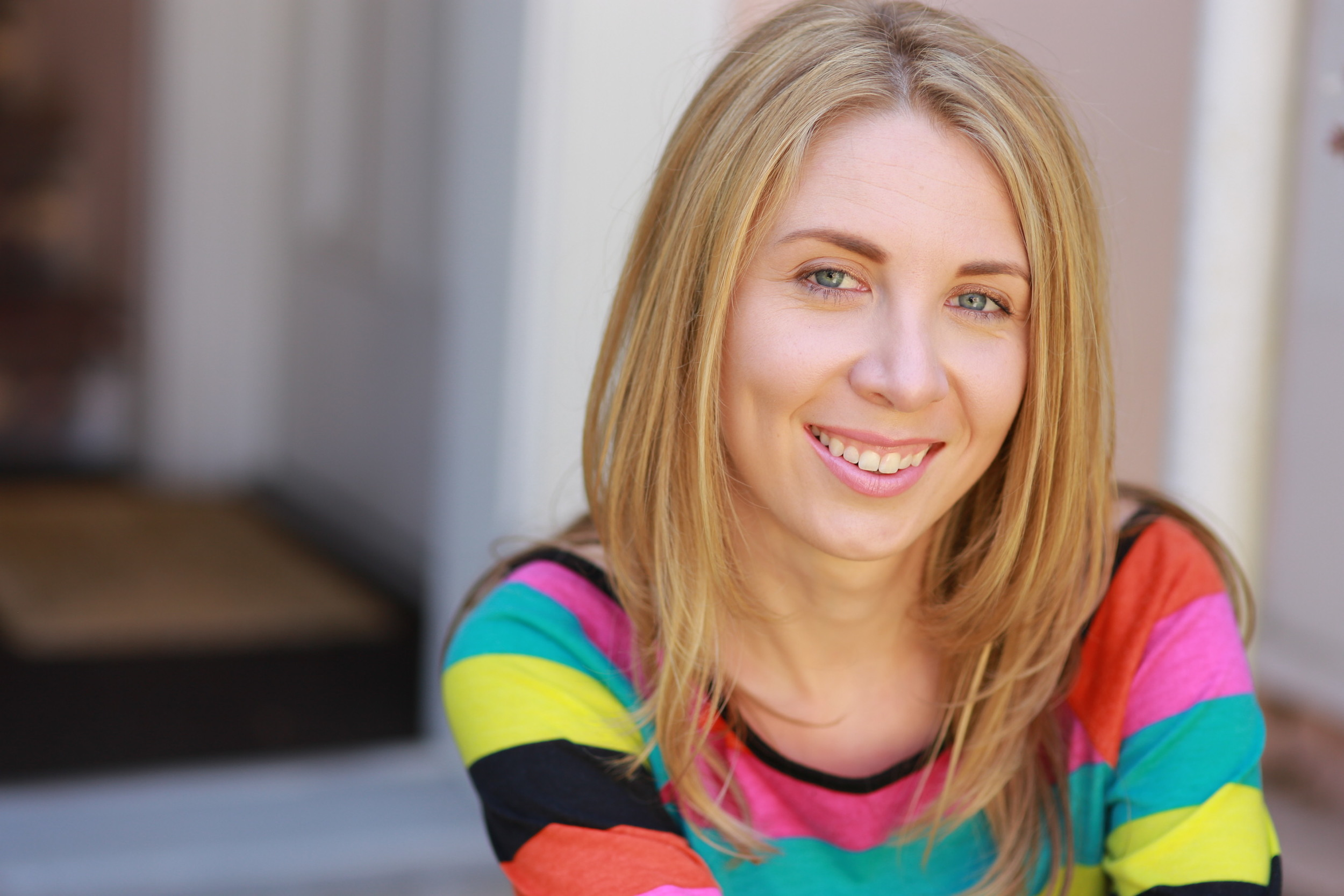 Alexandra's second headshot wearing a brightly color stripped shirt.