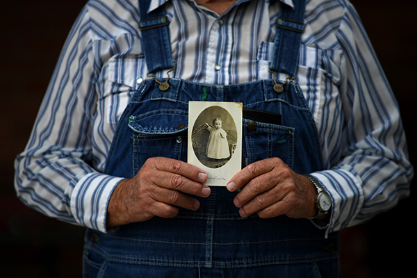 A man in Chadron, NE, holds up a photo of his mother when she was a baby, 103 years ago. She's still with us.