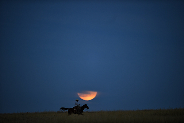 Tyler Messersmith rides across the super moon on his ranch in Lakeside, NE.