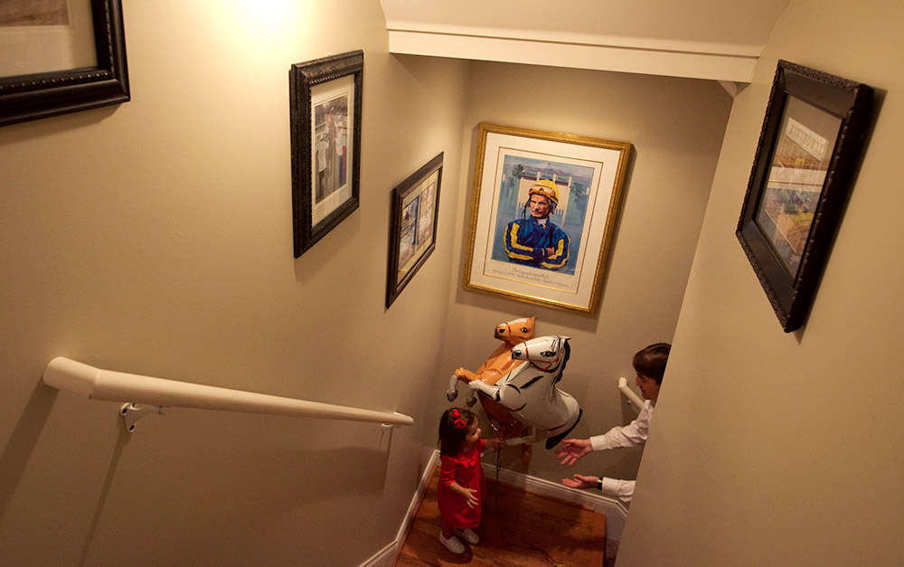 A portrait of legendary jockey Bill Shoemaker hangs in the stairwell of Hernandez's home in Louisville, as Hernandez and daughter Joshlyn play with horse balloons. Reminders of Hernandez's work are never far away, it seems.