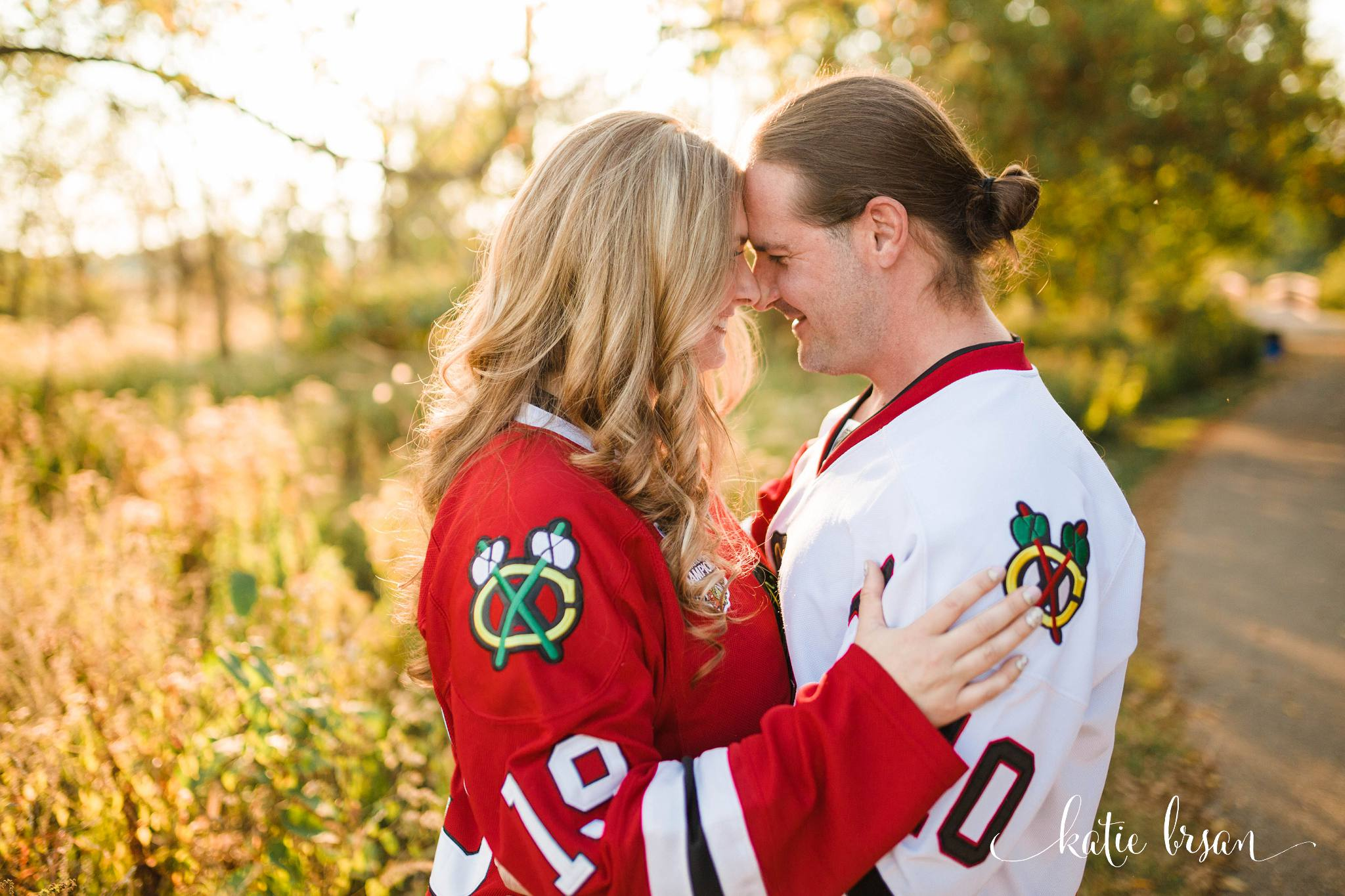 couple in hockey jerseys in forest preserve snuggling for engagement photos