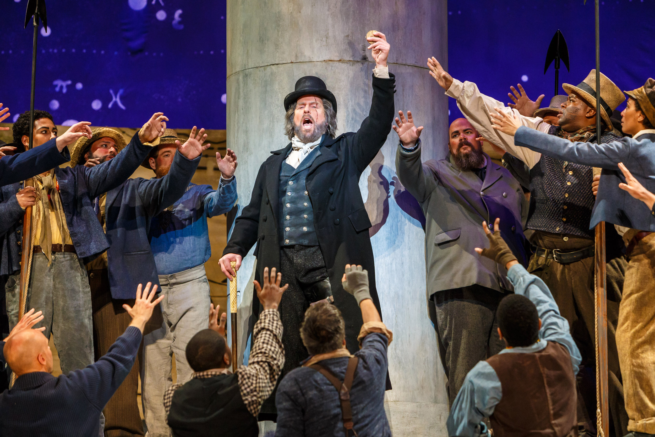 Roger Honeywell as Captain Ahab offers a gold doubloon for the man who first spots the white whale, Moby Dick.  Photo by David Bachman Photography; courtesy of Pittsburgh Opera.