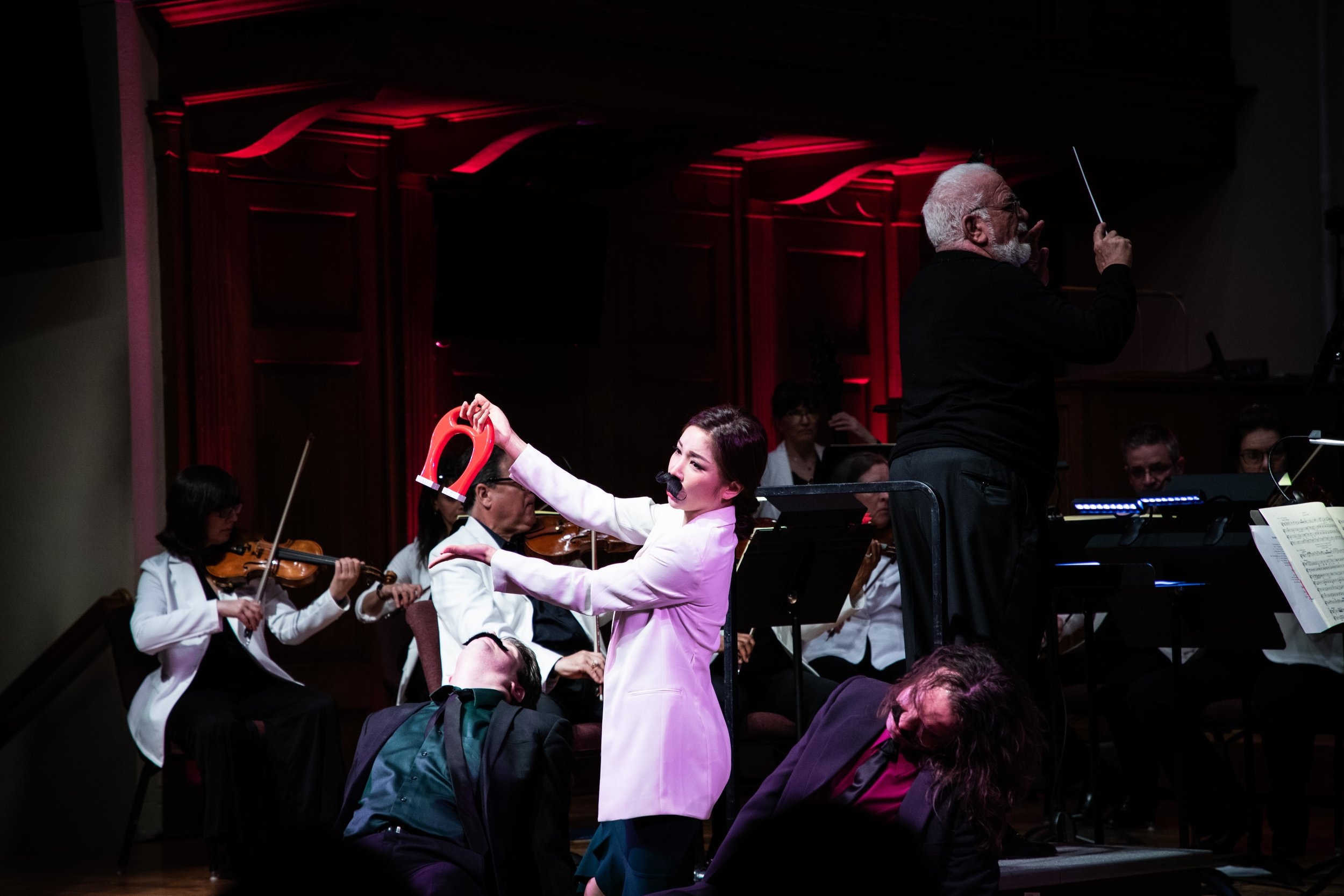 A comedic moment of  Cosi fan tutte ; soprano Nanyoung Song as Despina in disguise holds the magic cure for the passed out boys and, Conductor Louis Salemno holds the baton in the background. Photo by Sam Trotman; courtesy of Maryland Lyric Opera.