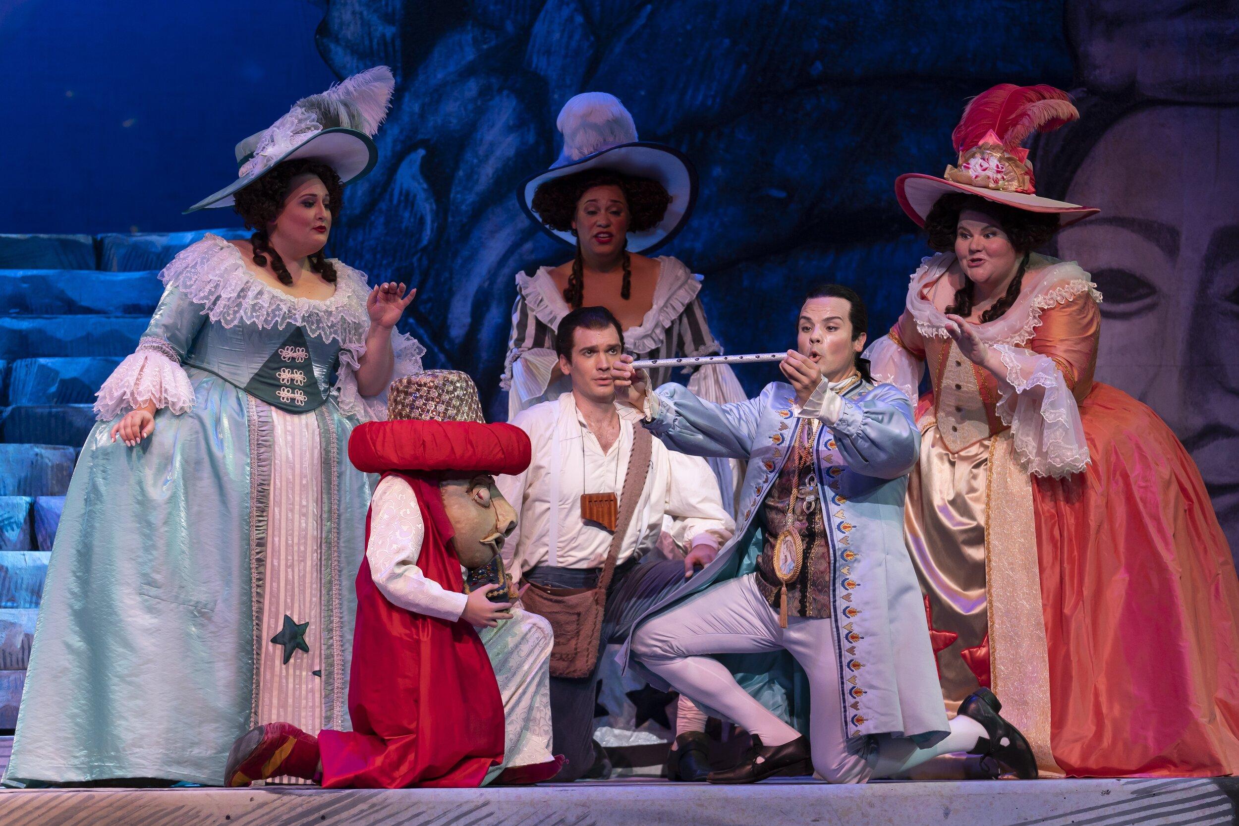 kneeling l to r : Michael Adams as Papageno and David Portillo as Tamino.  Standing :  l to r  the three ladies, Alexandria Shiner, Deborah Nansteel, and Meredith Arwady. Photo by Scott Suchman; courtesy of Washington National Opera.