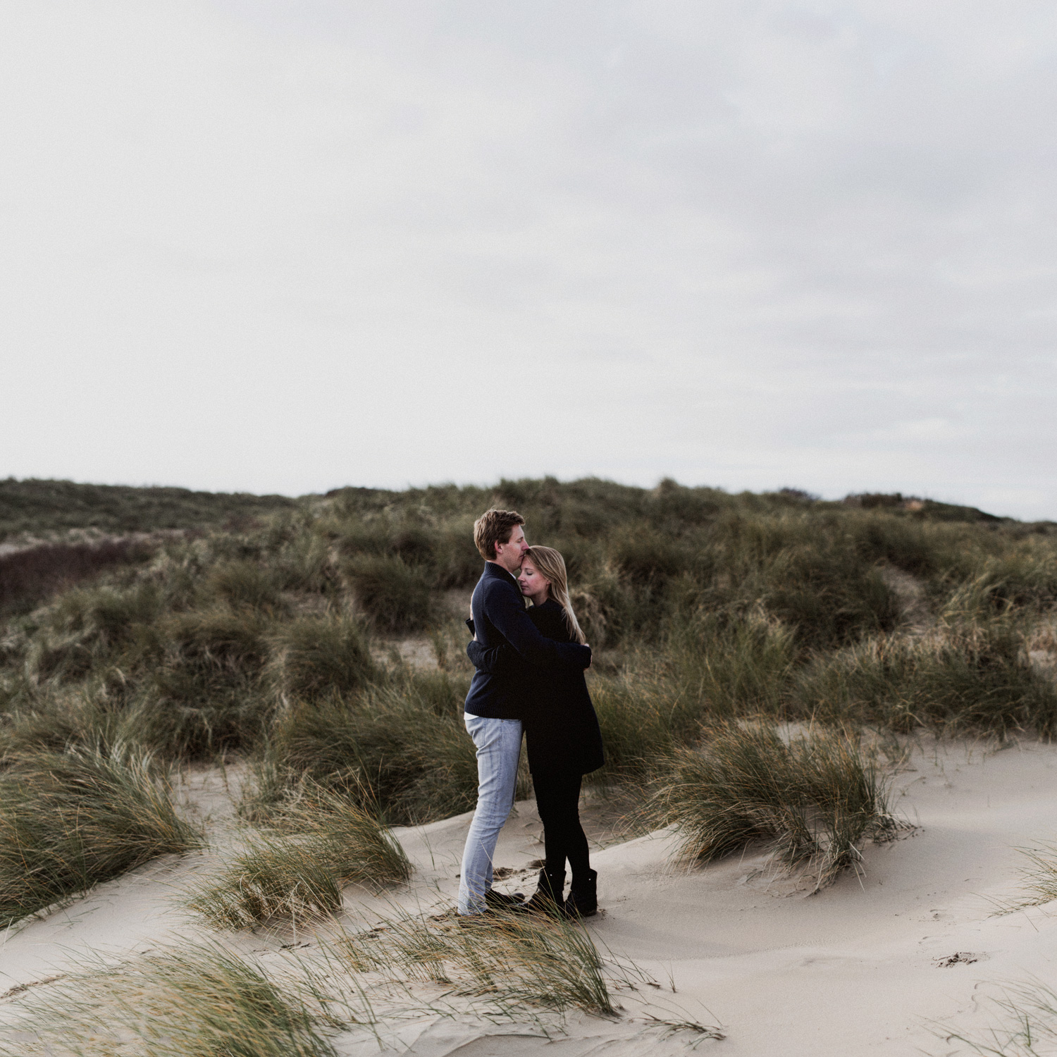 Couple standing facing each other in the dunes of Bloemendaal