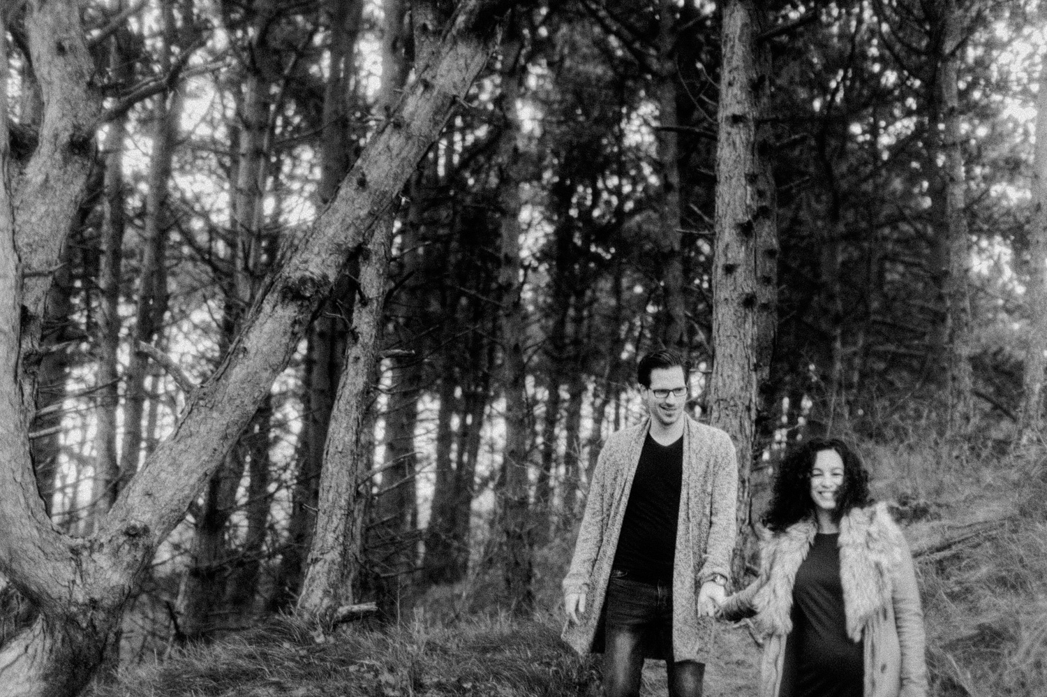 Couple walking holding hands and smiling in forrest