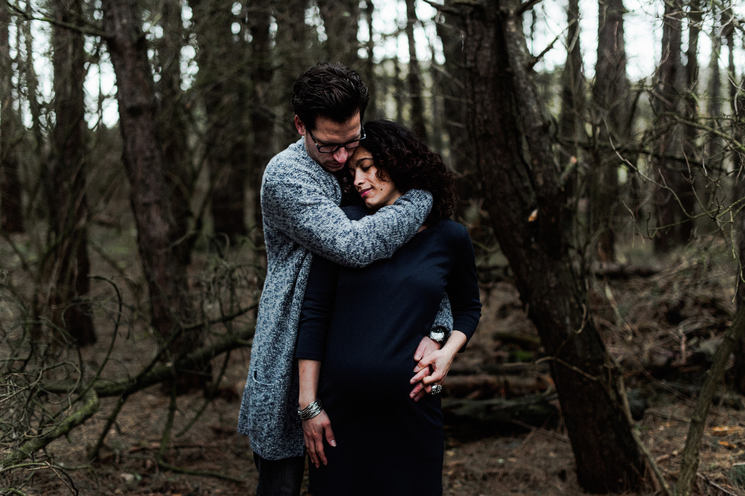 Close up of couple standing in forrest girl pregnant
