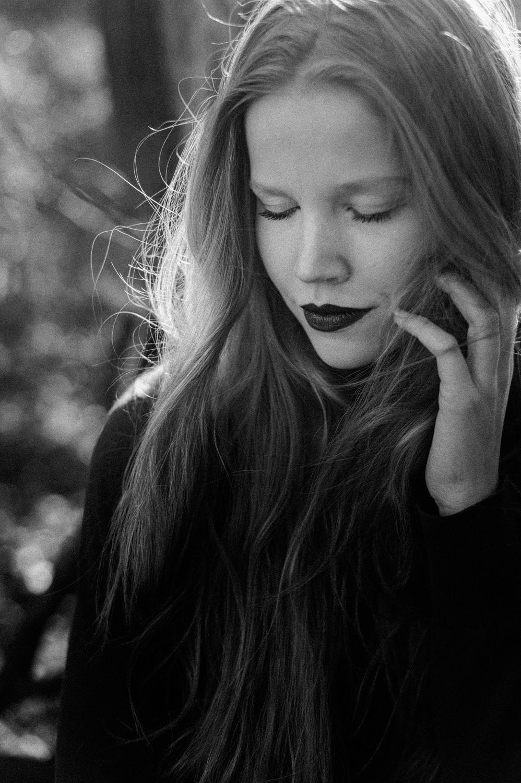 Fine art backlit portrait of girl touching her face