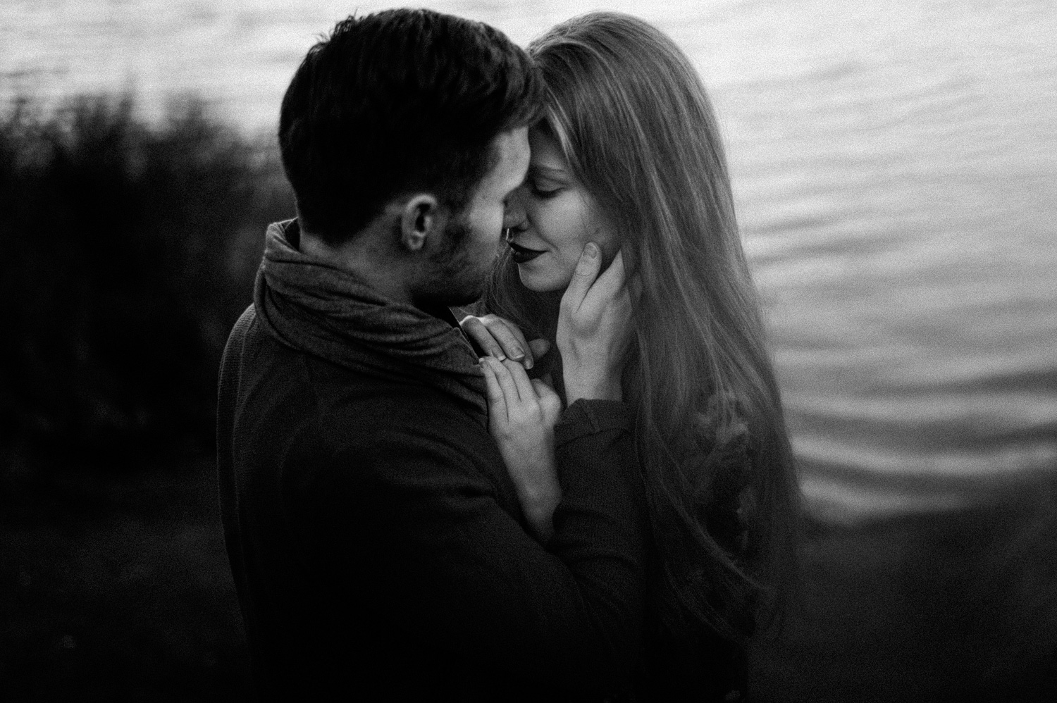 Couple facing holding each others faces in front of lake