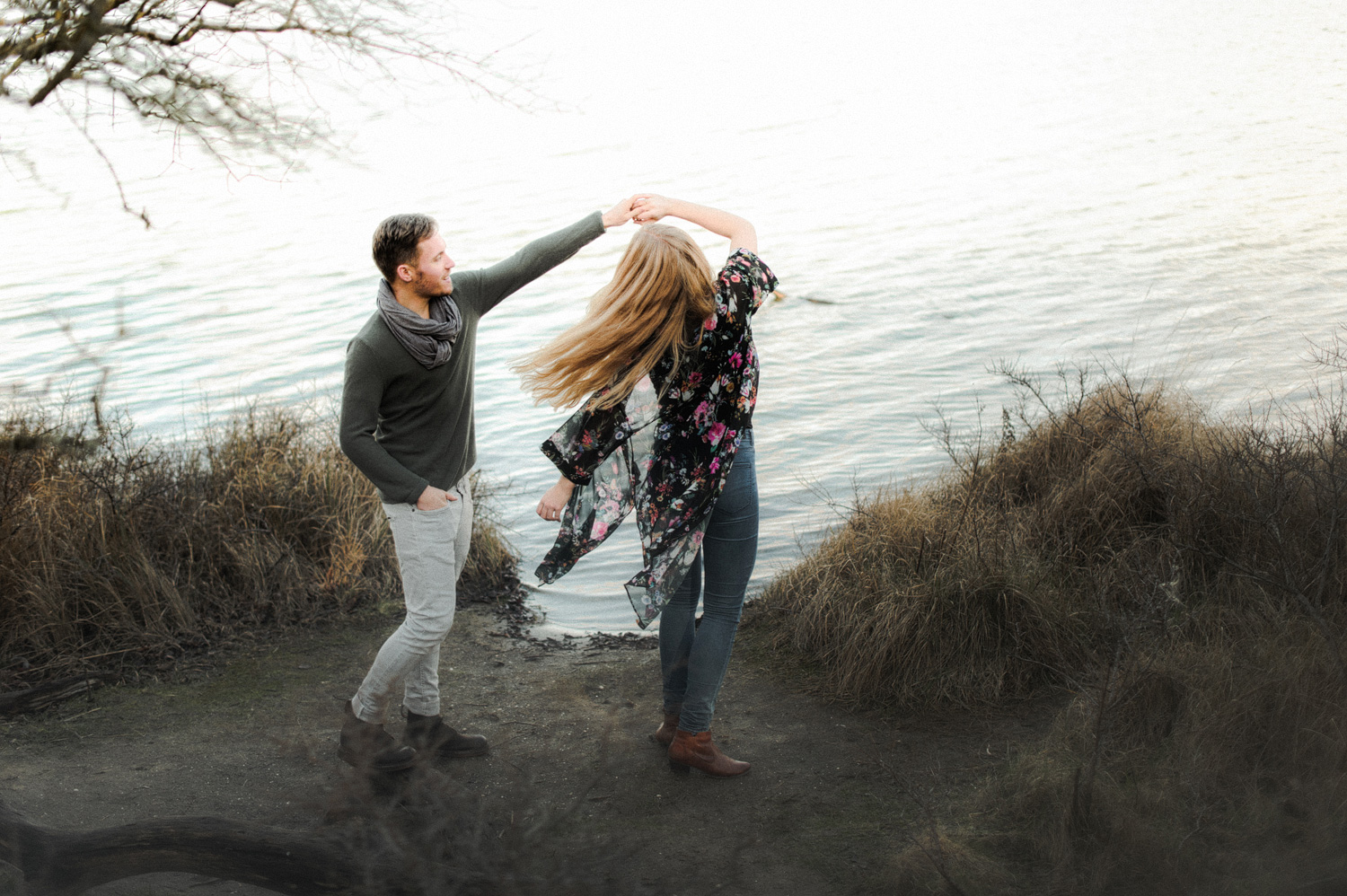 Couple dancing together in front of lake