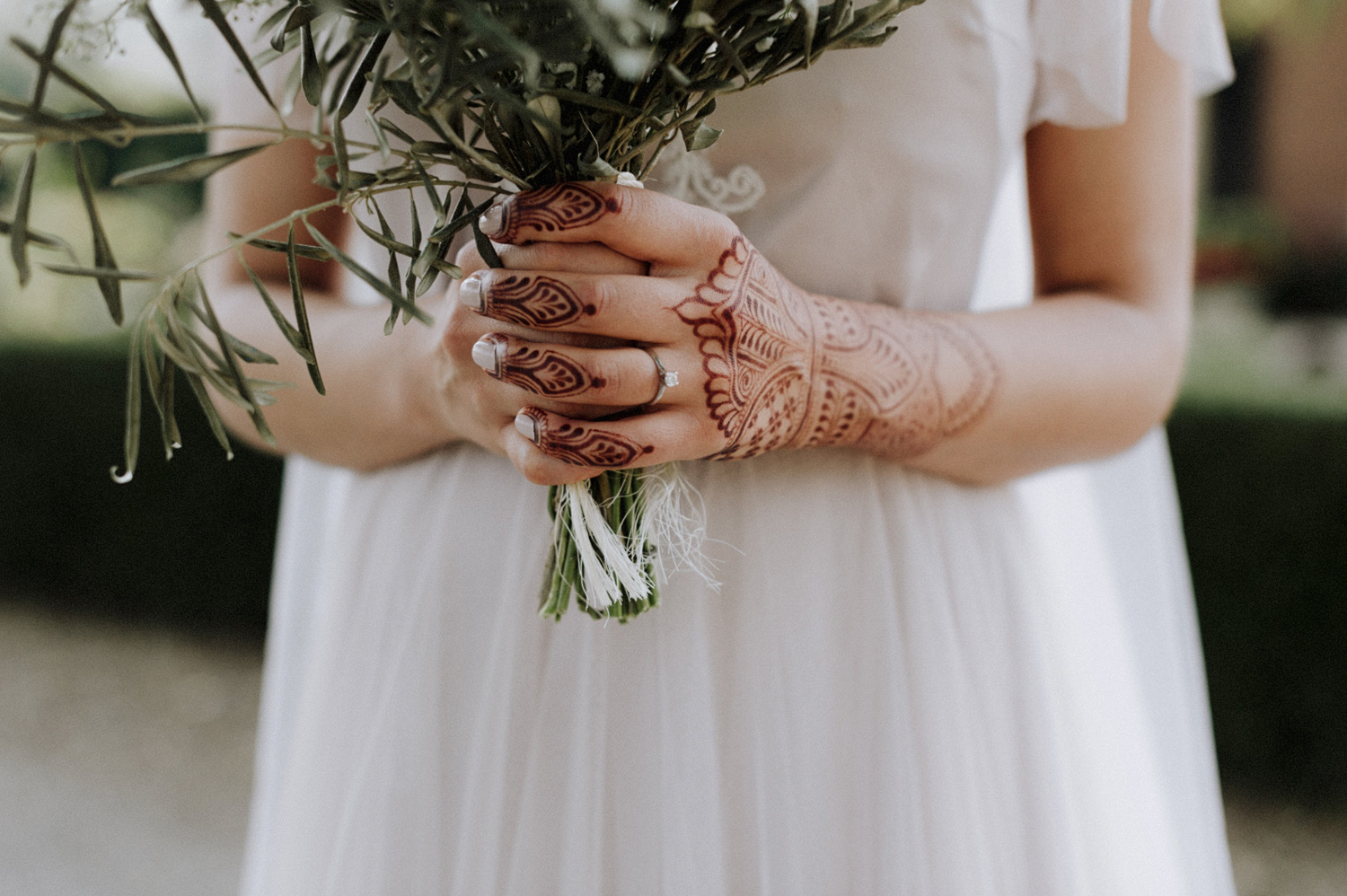 Bride holding bouquet with hands of henna