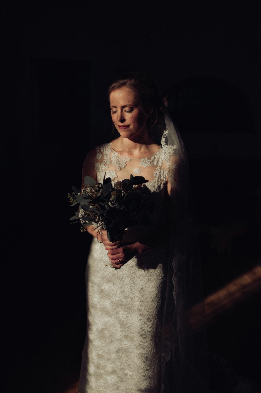 Bride holding bouquet standing in sunbeam with dark background