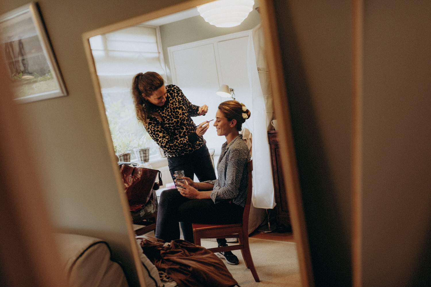 Bride getting her make-up done in mirror
