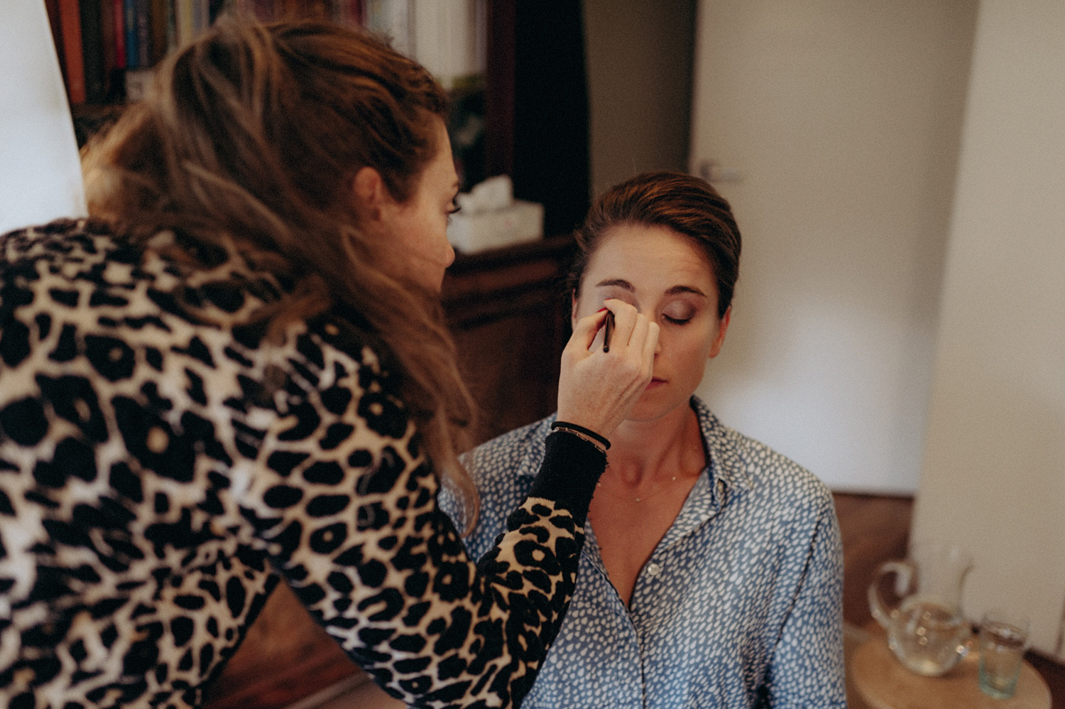 Bride getting her make-up done while getting ready