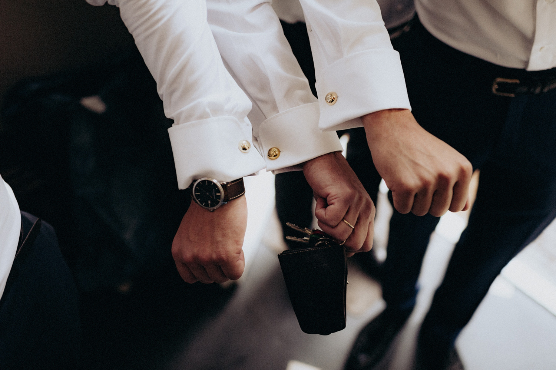 Groom and best man showing cufflink