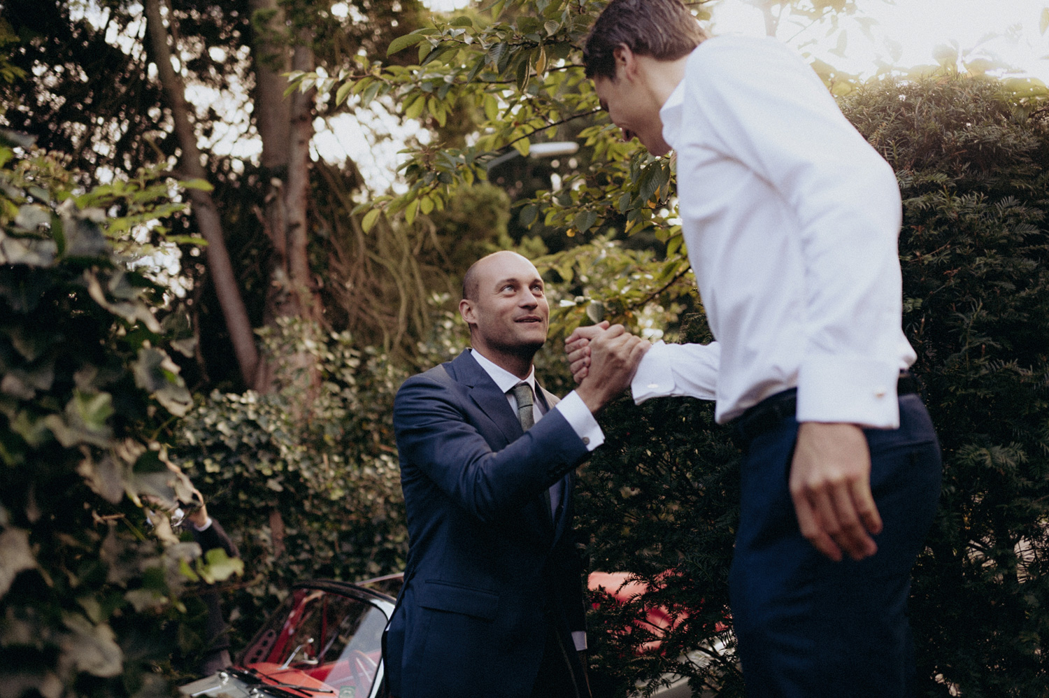 Groom shaking hands with friend in the woods