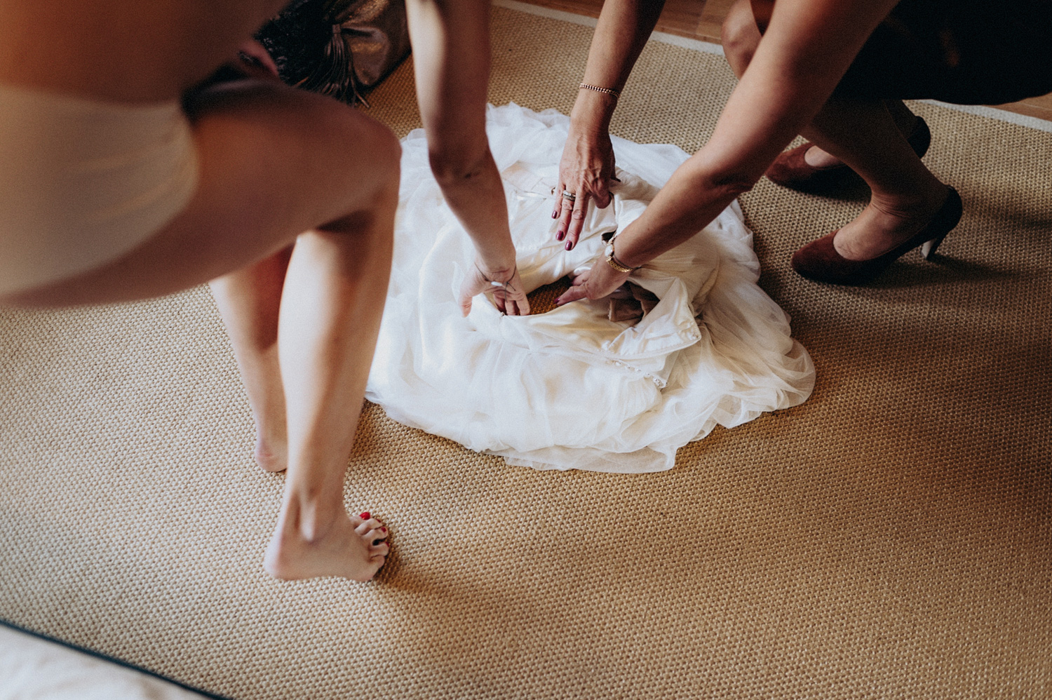 Bride stepping in her dress laid out on the floor