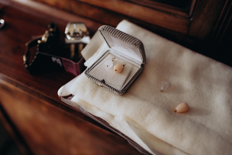 Earrings of the bride in box on cupboard