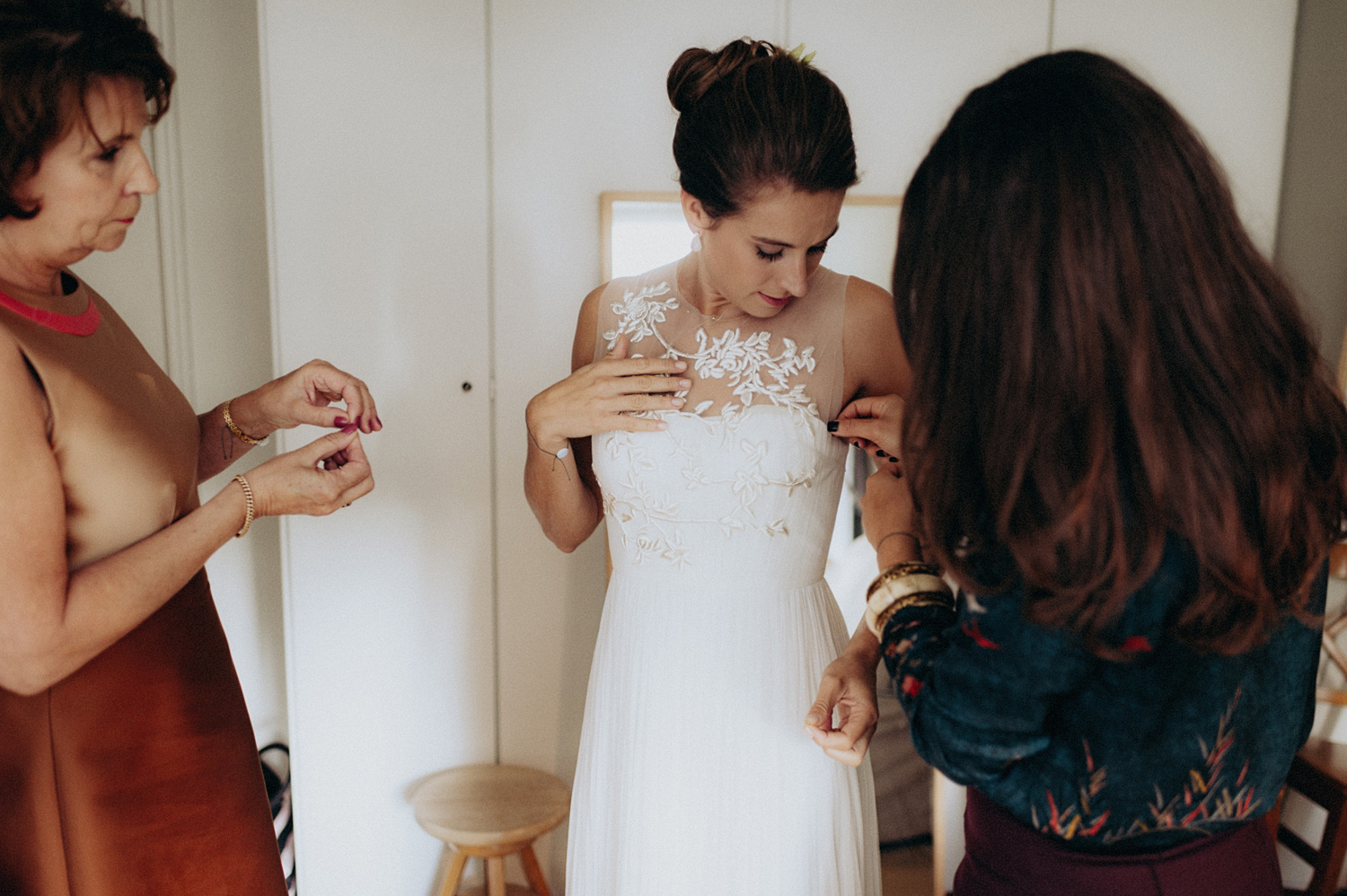 Bride with her mother and best friend putting on wedding dress
