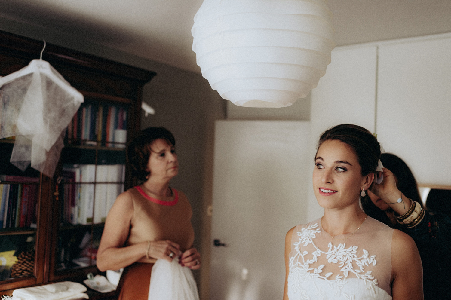 Bride smiling while getting ready with her mother