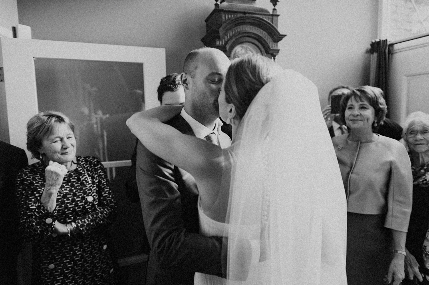Groom kissing his bride surrounded by weddings guests