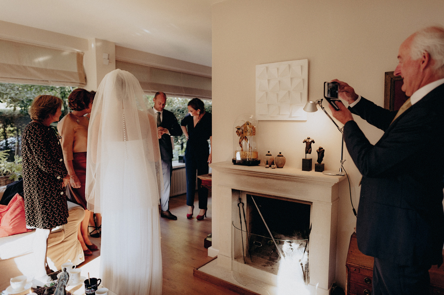 Weddings guest taking photo of bride with veil