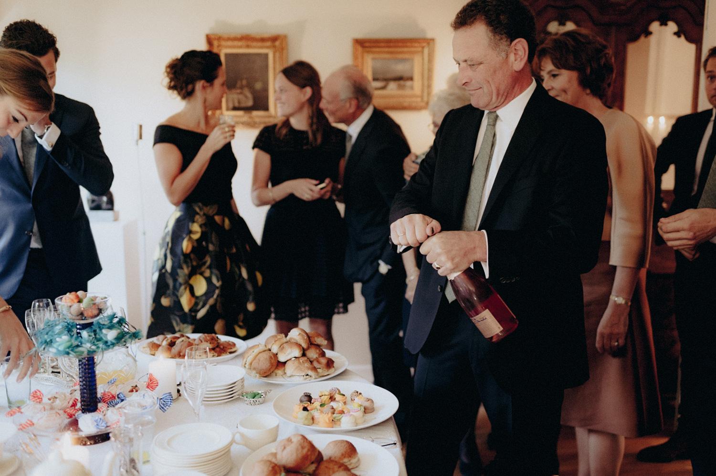 Weddings guest opening champagne bottle