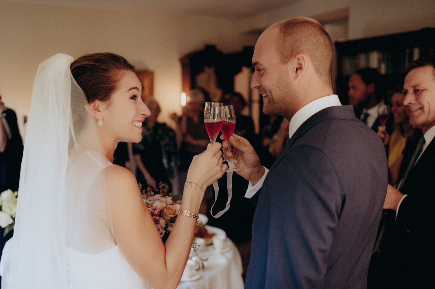 Groom and bride saying cheers with glasses of champagne