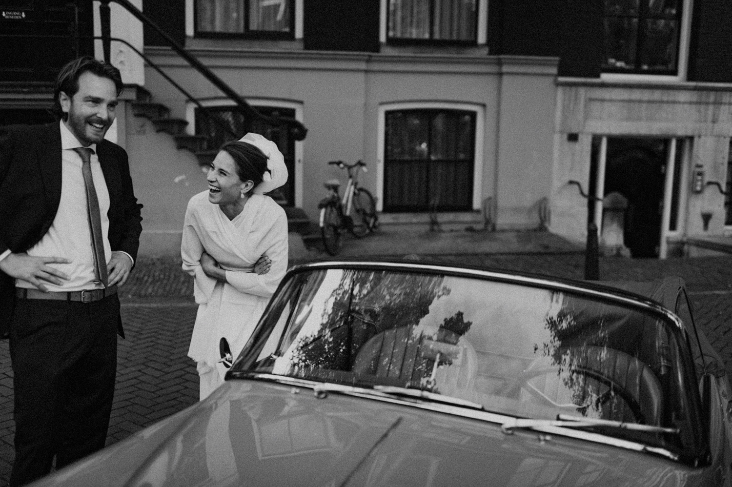 Bride laughing with wedding guest next to oldtimer car