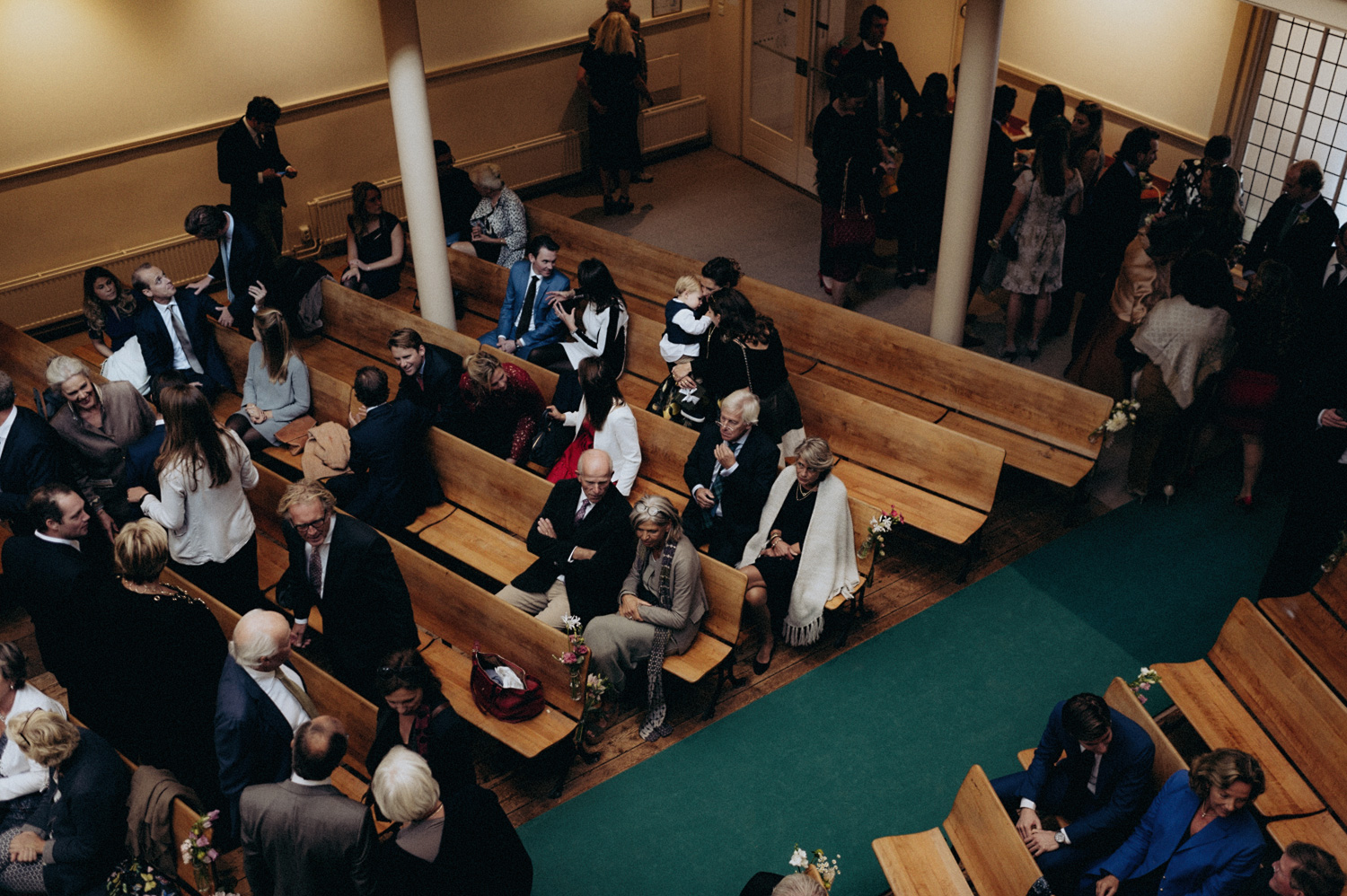 Wedding guests sitting in church benches at Keizersgracht Kerk Amsterdam