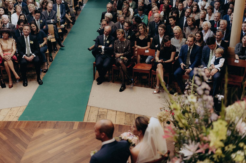 Bride and groom looking at their wedding guests in Keizersgracht Kerk Amsterdam
