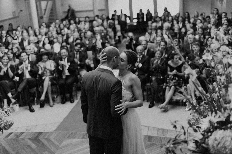 Bride and groom kissing wedding guests in the background at Keizersgracht Kerk Amsterdam