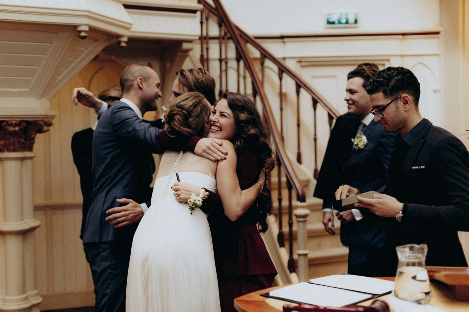 Friends of bride and groom hugging couple