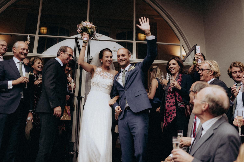 Bride and groom leaving Keizersgracht Kerk Amsterdam while smiling