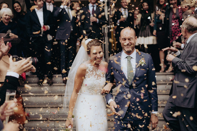 Bride and groom leaving Keizersgracht Kerk Amsterdam while wedding guests cheer