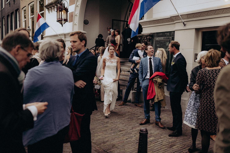 Wedding couple leaving Keizersgracht Kerk Amsterdam with dutch flags