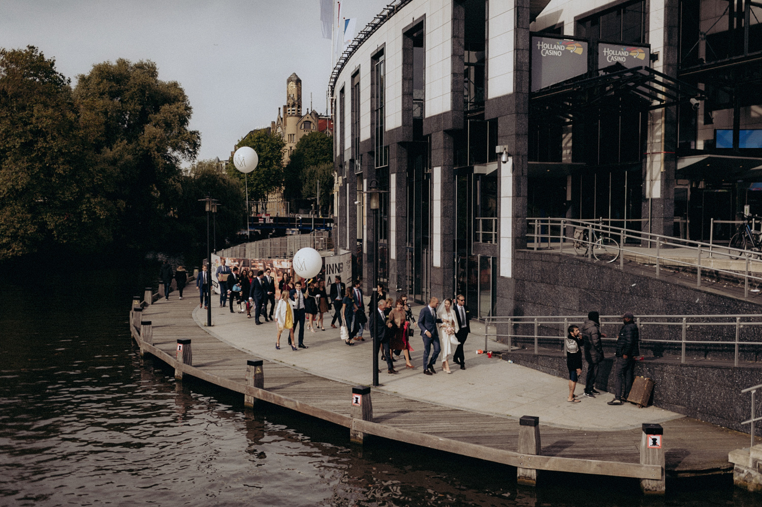 Wedding guests walking past canals close to Leidse square in Amsterdam