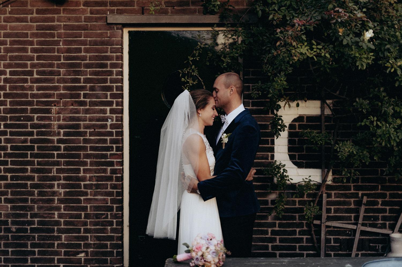Groom kissing forehead of bride at Rijk van de Keizer