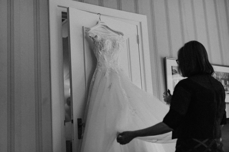 Mom of bride putting dress on door