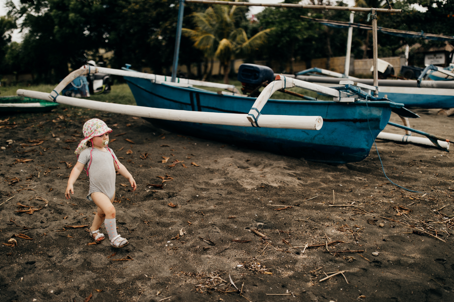 Kid walking next to boat on the beach in Bali, Indonesia