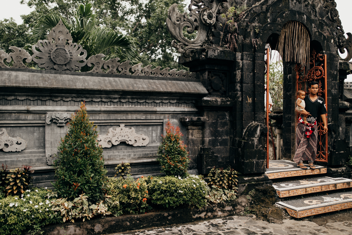Father with kid on arm at temple entrance in Bali, Indonesia