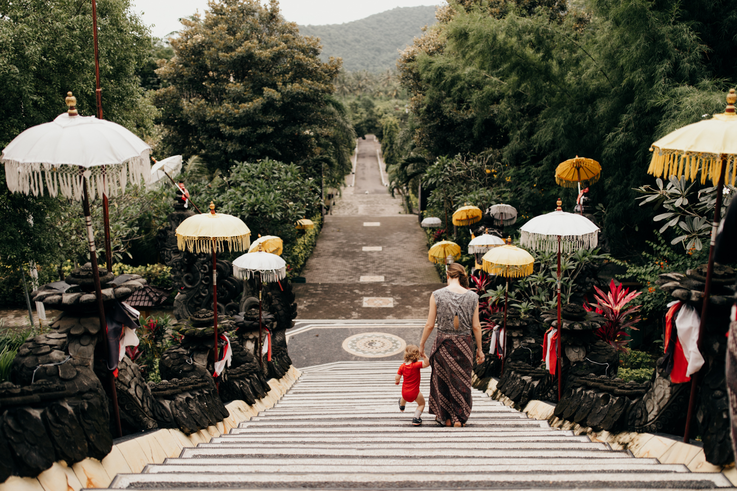 Kid walking temple stairs with mother in Bali, Indonesia