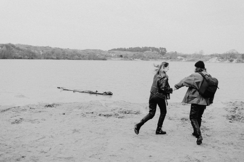 Couple running around at beach near lake
