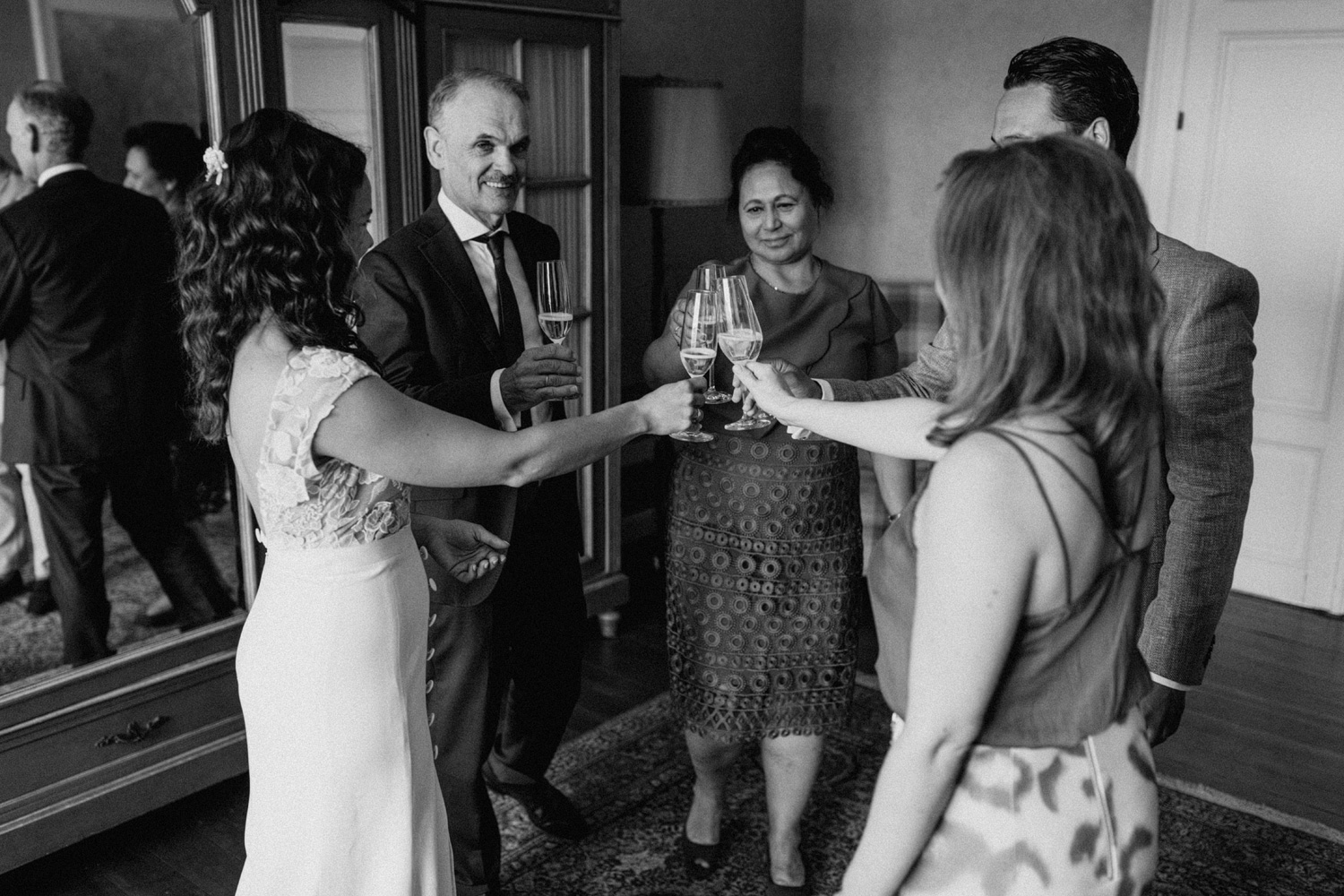 Bride drinking champagne with friends and family