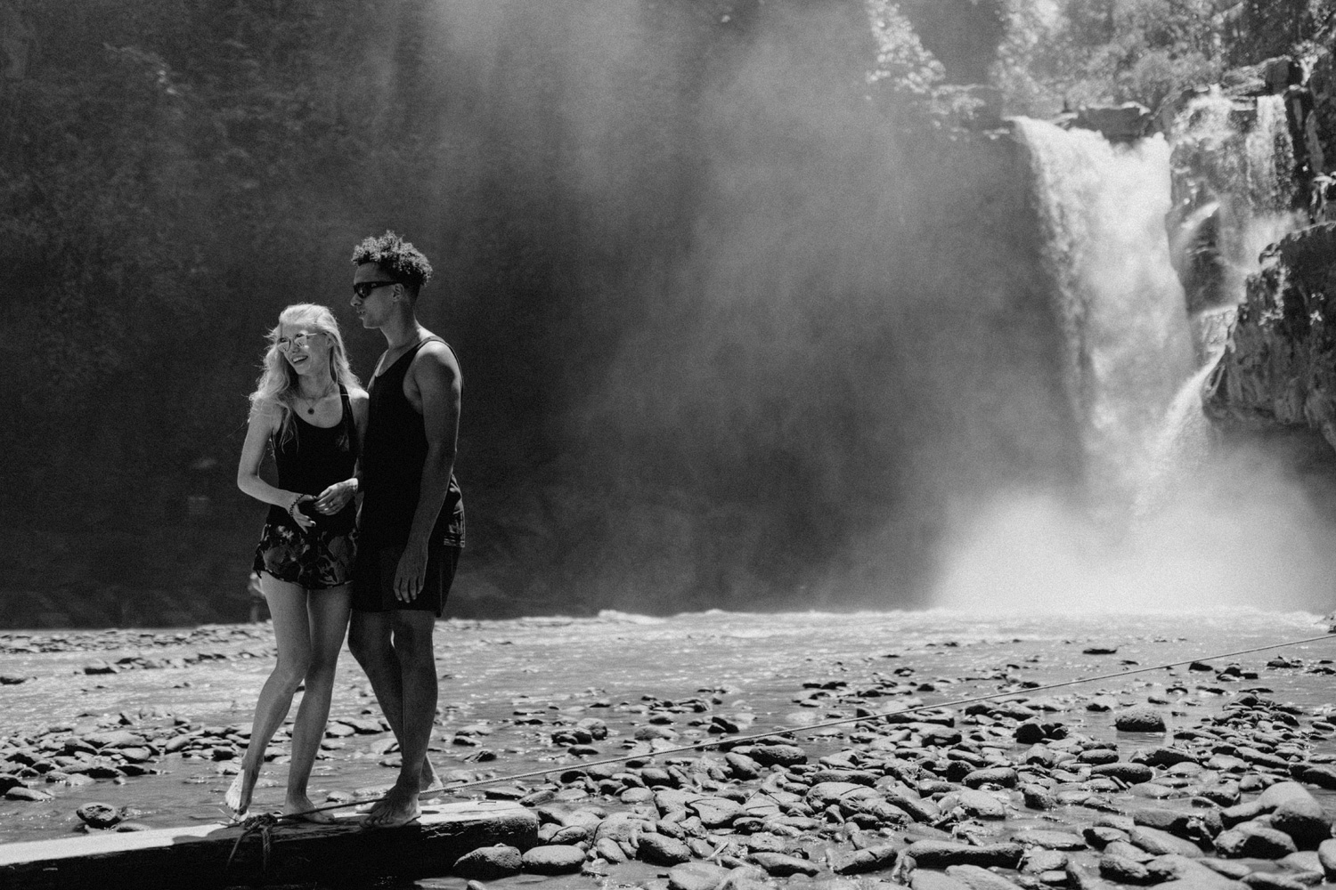 Couple holding each other in front of Tegenungan Waterfall, Bali