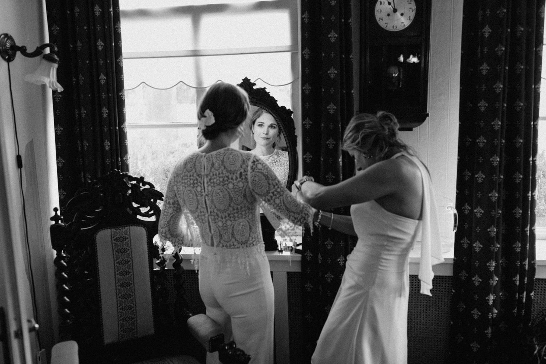 Bride preparing in dress seen through mirror