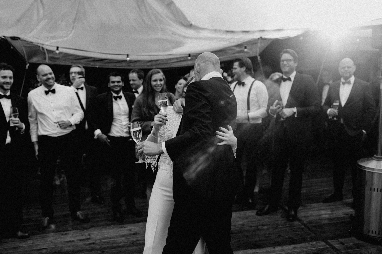 Dancing bride and groom between their guests