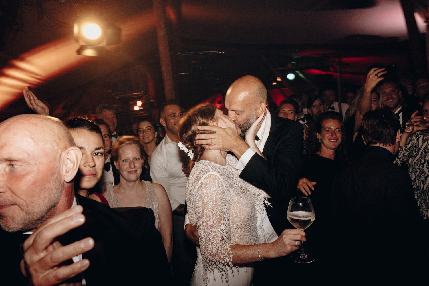 Bride and groom kissing on the dancefloor shot with flash