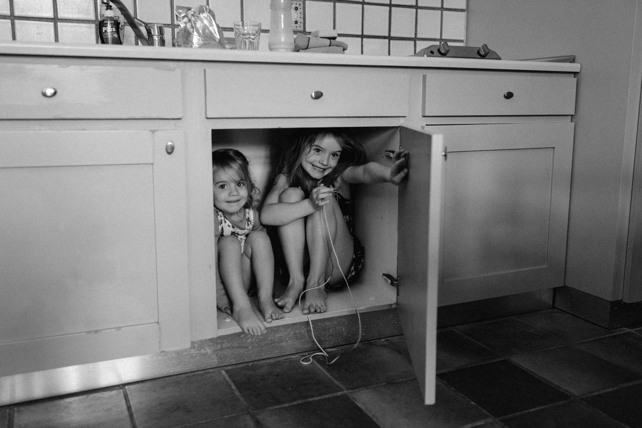 Sisters hiding in cupboard under sink