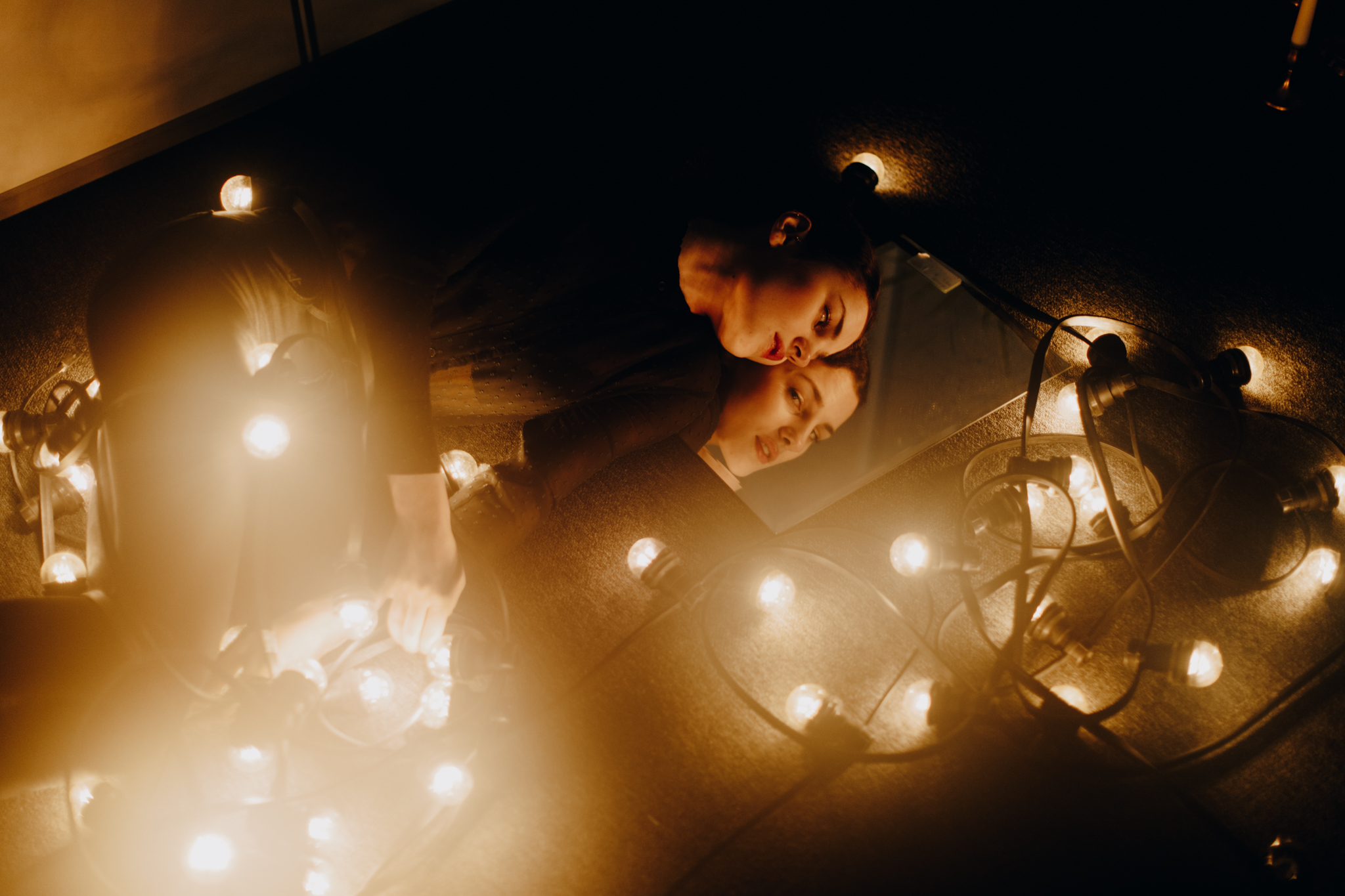 Girl looking in mirror surrounded by string lights